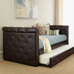 Dark tufted leather daybed with light blue upholstery and additional trundle