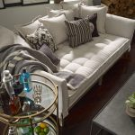 Daybed with white tufted upholstery some throw pillows
