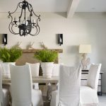 Elegant White Dining Room With White Slipcovered Dining Chairs Wrought Iron Chandelier And Ceiling Beams