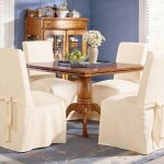 Four White Slipcovered Dining Chairs With Small Wooden Dining Table Corner Cabinet And Decorative Rug
