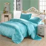 Glossy turquoise bedding for a classic bed frame with classic curved headboard a white classic bedside table with drawers a bedroom vanity in classic style