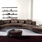 Half curved couch in brown round center table with cushion some throw pillows with dark brown motifs free standing wood rack for organizing decorative items
