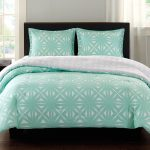 Light turquoise and white reversible bedding set for standard size bed a bed frame with black headboard