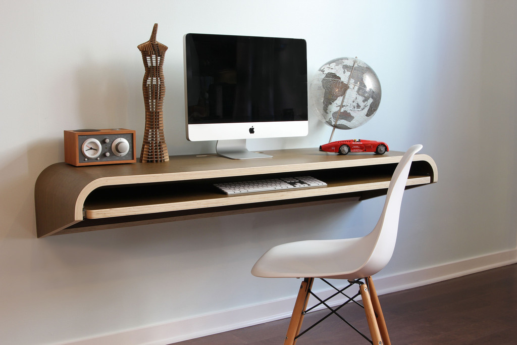 Minimalist floating computer by IKEA a white chair with wood made legs