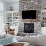 Natural Stone Fire Places With White Furniture In Living Room And Fan On Beams Ceiling