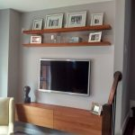 Simple minimalist wall media shelves made of wood a wall mounted TV set two sets of wall shelves for organizing pic frames a corner chair