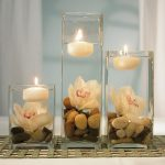 Three pieces of candle decoration that is put on transparent glass contained water white flower and natural river stones