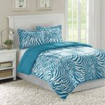 Turquoise and white bedding set in zebra motif a bed frame with higher white headboard a white bedside table with drawer white fluffy rug for bedroom