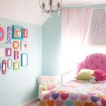 Twin size bed frame with cute pink headboard a small corner chair with pink motifs light blue wall system with a group of pic frames