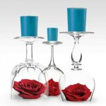 Unique candle centerpiece for table which consists of upside down wine glass and blue candlestick over it