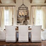 White Slipcovered Dining Chairs With Real Candle For Chandelier And Exposing Beams For Ceiling
