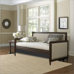 White upholstered daybed with dark wood frame