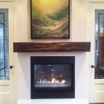 Wood Fireplace Mantel In Rustic Style Installed Over Black Framed And Glass Door Fireplace Unit