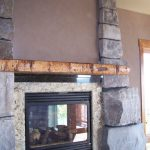 Glass Door And Wrought Iron Framed Fireplace Garnished With A Reclaimed Wood Mantel