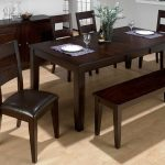 Dark finished wooden bench with dark leather cushioned dining chairs