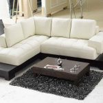 Modern white sectional sofa in L shape dark finished wooden coffee table fluffy gray area rug in small size