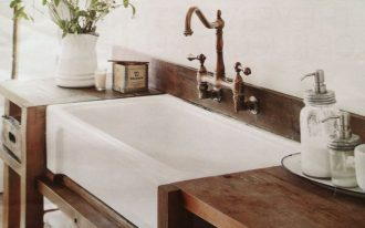 Oversize farm sink in white with bronze water faucet in a bathroom