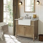 White bathroom farm sink with single water faucet a bathroom vanity made of unfinished wood a pair of vanity lamps