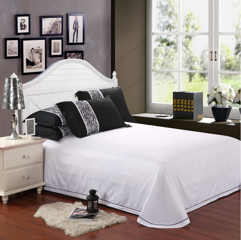 luxurious white bedding set with dominant black shams a bed frame with pointed white headboard a