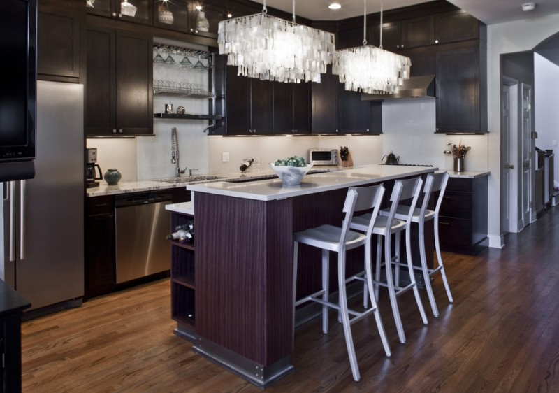 L shaped eat in kitchen model with dark toned cabinets white countertop white top island and mini bar white stools stainless steel appliances white subway tiles backsplash medium toned wood floors