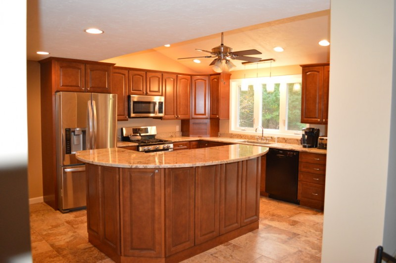 L shaped kitchen with tier island dark wooden cabinets luxurious granite countertop expensive granite island stainless steel appliances ceiling fan beige granite flooring idea