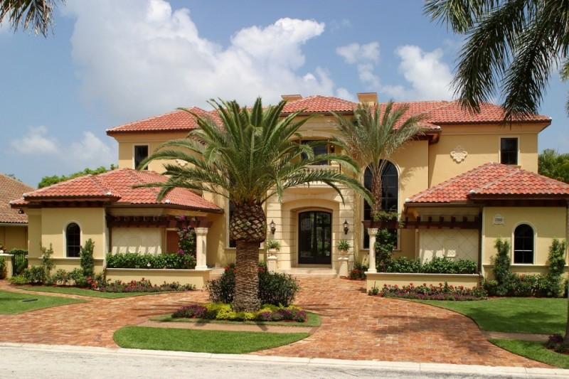 Luxurious Tuscan style home idea with terracotta roof system light yellow wall system large fron yard and path dark wrought iron door and windows