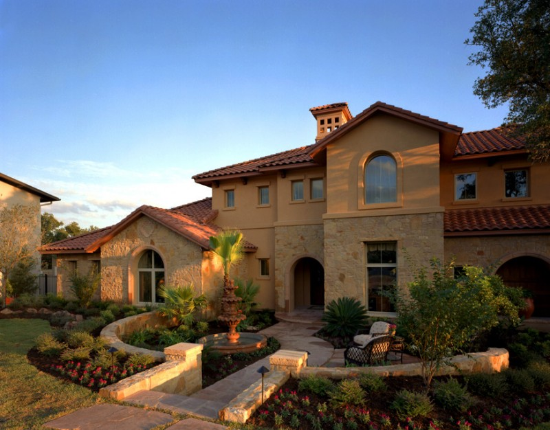 Mediterranean and Tuscan style house with half stone and stucco walls curved top windows and doors good mainted courtyard