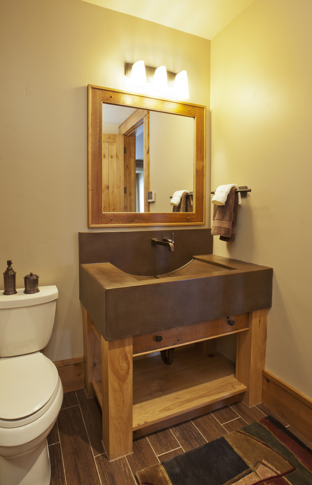 Western themed bathroom vanity with wooden framed vanity mirror darkwood tiles floors and vanity lamps on top