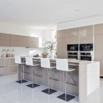 Beige Minimalist Open Kitchen Plan With White Bar Stools Beige Flat Panel Cabinet System Stainless Steel Appliances White Ceramic Floor I Shaped White Countertop