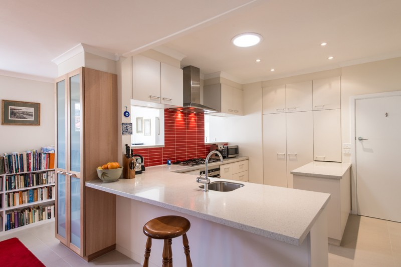 contemporary L shaped kitchen integrated with kitchen island rectangular red backsplash undermount sink stainless steel appliances minimalist white cabinets wooden cupboard with glass door