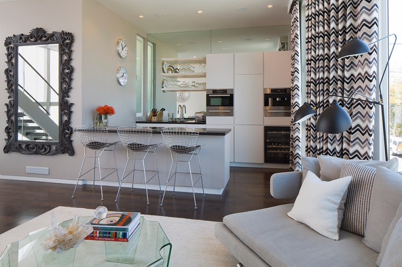 contemporary and stylish small open kitchen concept with light metal net stools a classic framed mirror a family room