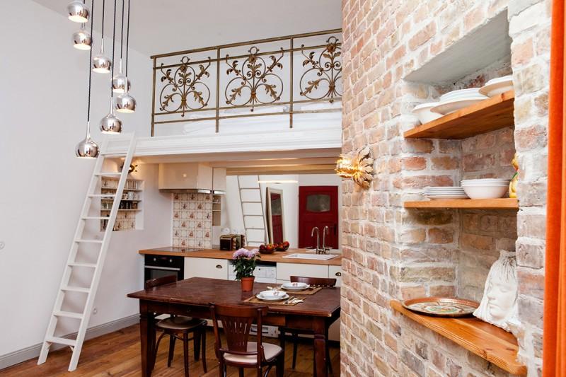 cottage chic open kitchen design with wooden open shelves white cabinetry darkwood dining furniture set medium toned wood countertop mirror backsplash original bricks wall system