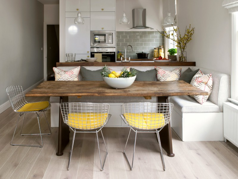 dining side chairs with yellow seating hardwood rectangular table L shape sofa with accent pillows pale toned wood floors grey subway tiles backsplash wood countertop stainless steel appliances