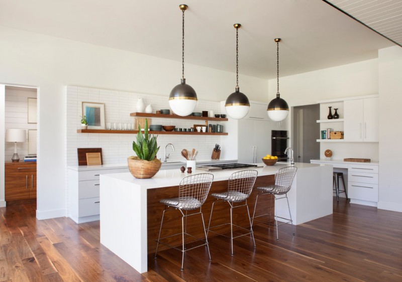 eclectic mid century L shape kitchen with industrial pendant lamps chrome stools white flat panel cabinet extra long island walnut floors wooden open shelving for kitchen and dishware white subway tiles