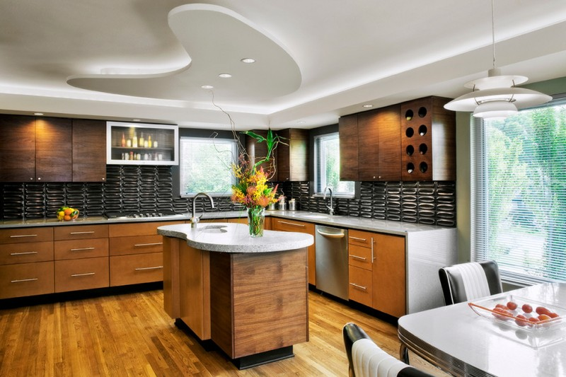 elegant and modern L shaped kitchen idea with textured and patterned black backsplash white granite island flat panel kitchen cabinets and undermount sink