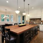 Grand And Luxurious Kitchen And Dining Room Half Circular Sofa Oval Shape Black Dining Table Hardwood Top Island Black Solid Stools White Cabinetry Bricks Backsplash Black Solid Countertop