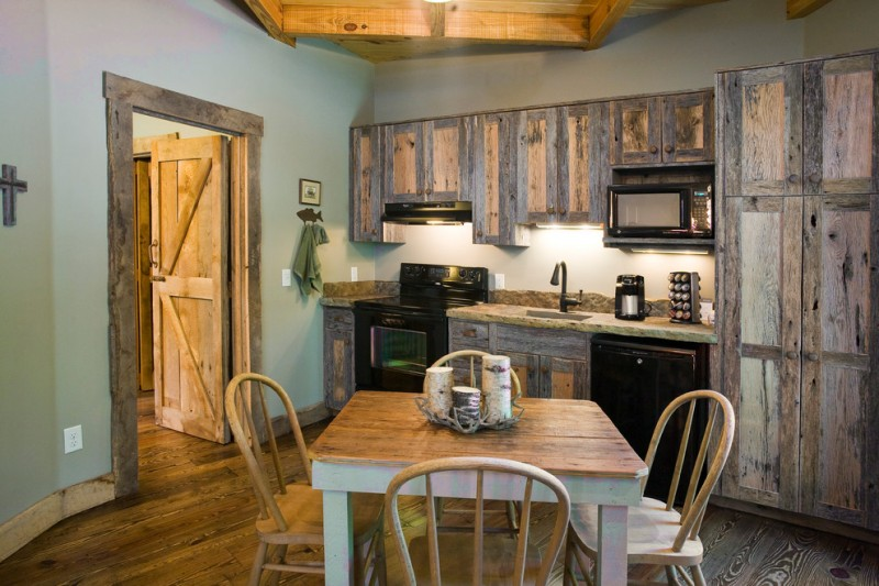 kitchen cottage with Western style shabby wooden cabinets and cupboard black finished appliances wooden dining furniture without finishing wooden countertop medium tone wood floors