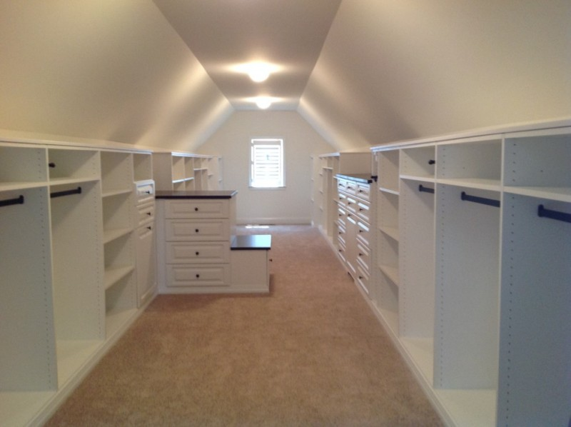 long walk in closet idea with white storage options ceiling lamps hardware and dark wood accents