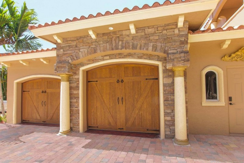 luxurious mediterranean garage door concept with darker limestone wall system and cream frame