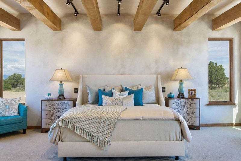master bedroom in Western theme a large bed with white headboard light beige bed linen colorful pillows twin of side tables with patterns in fronts bright blue corner chair large wood logs on roofs
