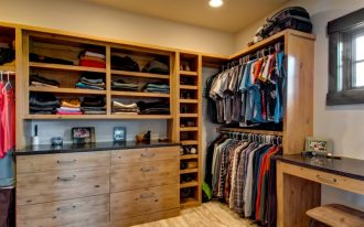 men's walk in closet idea with flat panel cabinets and medium hardwood floors