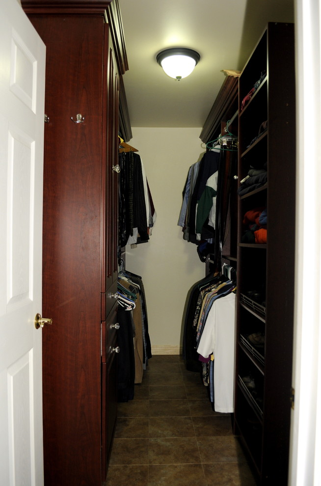 men's walk in closet with darker wooden finsih and bulb ceiling light and white craftsman door