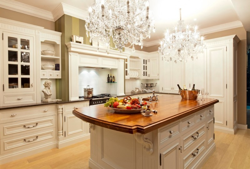 mid size and eat in kitchen design with L shaped counter and wood top island two crystal chandeliers giant white cupboard
