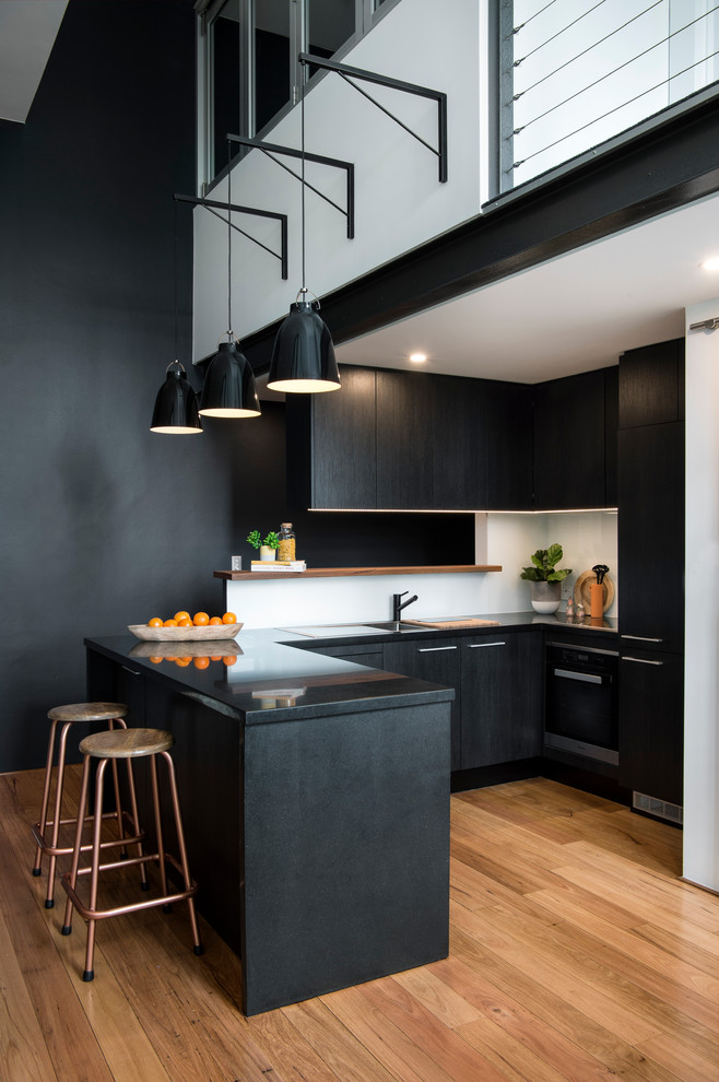 minimalist gothic small open kitchen black painted cabinetry gloss and black bar table copper toned bar stools gloss black kitchen counter purely white backsplash medium toned hardwood flooring idea