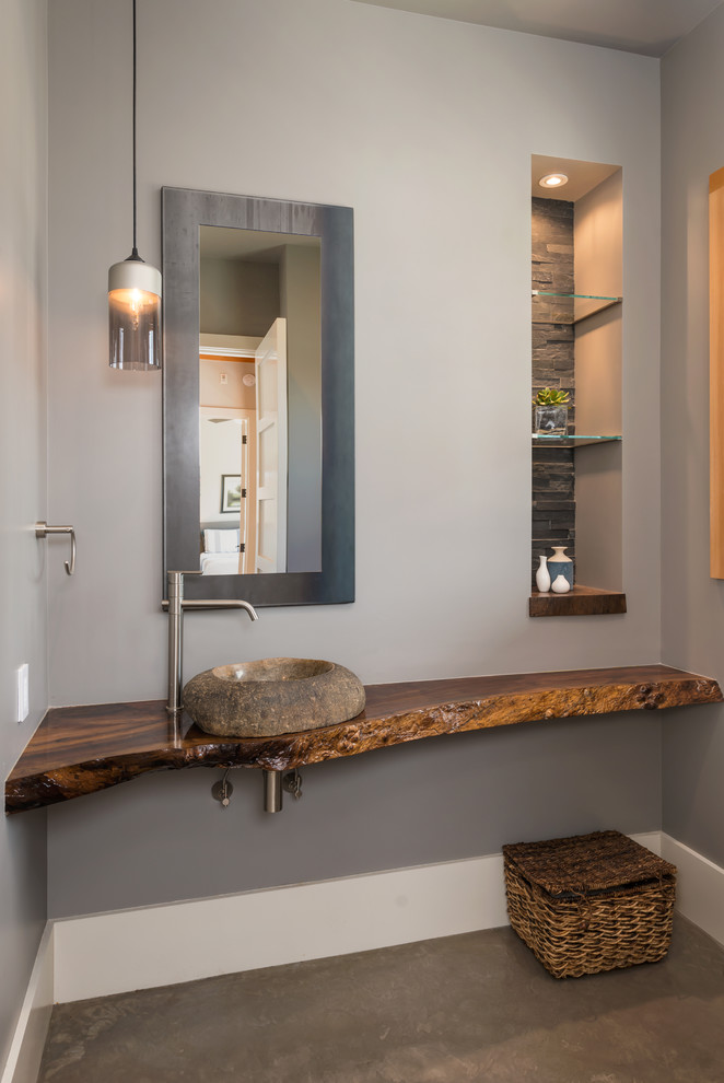 modern Western bathroom vanity idea log countertop vanity vessel made of natural stone rattan basket modern metal framed mirrors modern hanging lamps recessed shelves with lamp on top