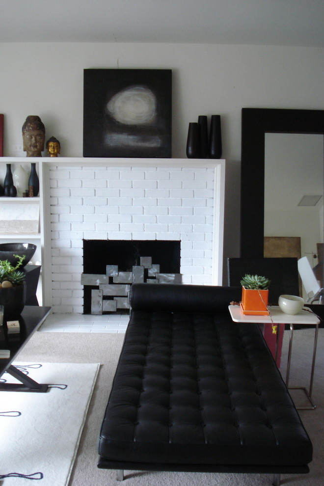 modern white brick fireplace with lightweight metal cover a black cushion sofa