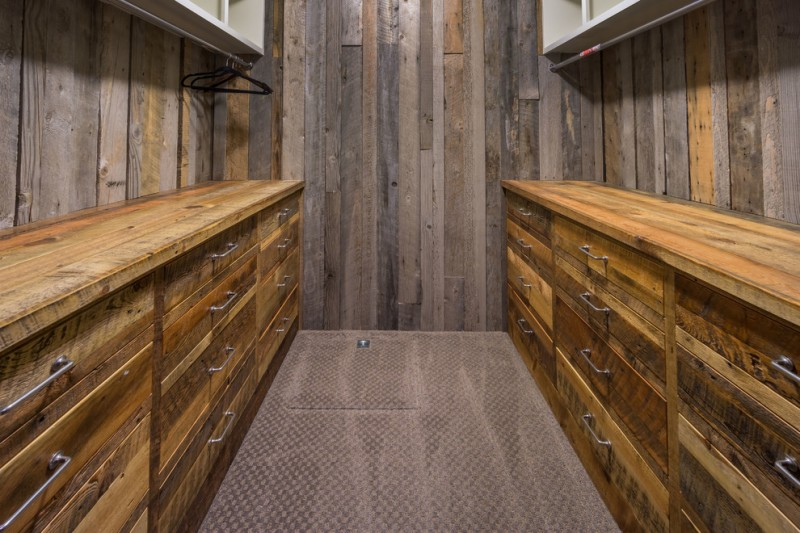mountain style walk in closet idea old yet stylish wooden slabs walls idea medium tone wooden cabinet system with flat panel long hang sections with metal pipe white open shelves