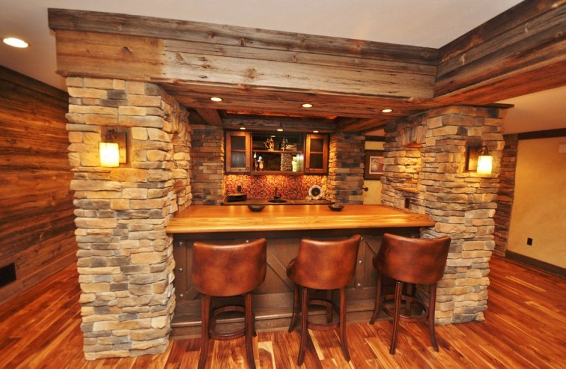 raw rustic basement bar idea with bar stools wood top bar table mosaic backsplash open shelves bricks walls beam cover floors