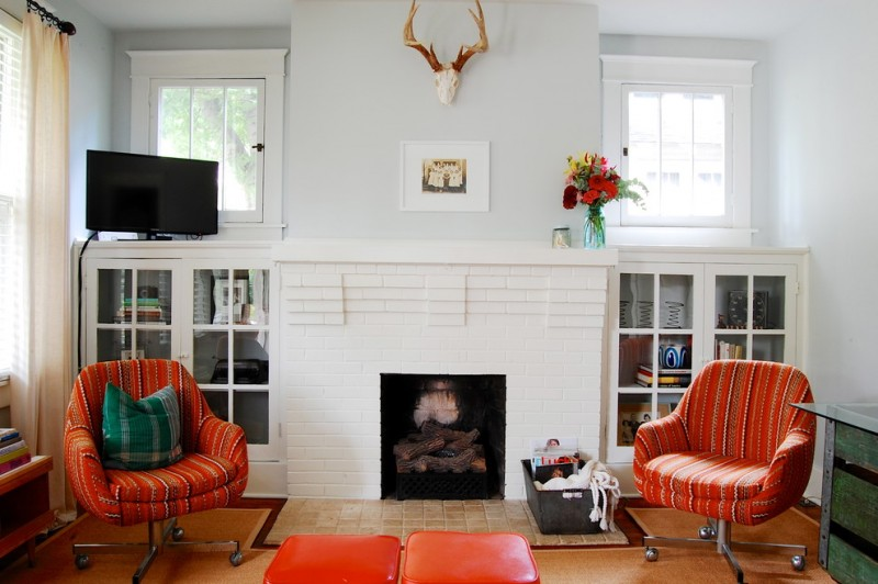 reading nook with wall mounted white bricks fireplace and glass door book shelves a pair of reading chairs with wheels