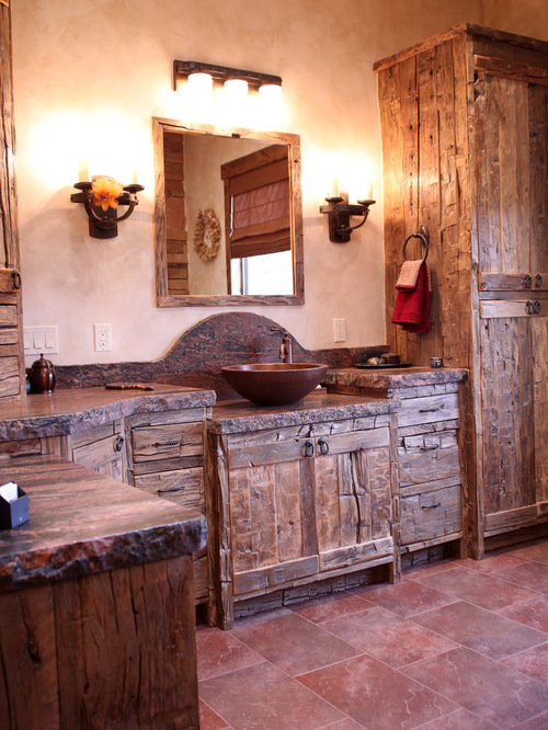 rustic bathroom vanity with dark granite countertop dark vessel dark wood framed vanity mirror a couple of wall lamps